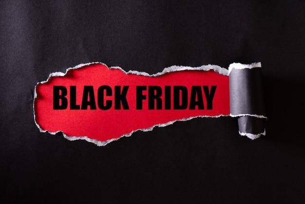 Zwart gescheurd papier en de tekst black friday op rood