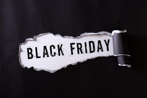 Zwart gescheurd papier en de tekst black friday op wit.