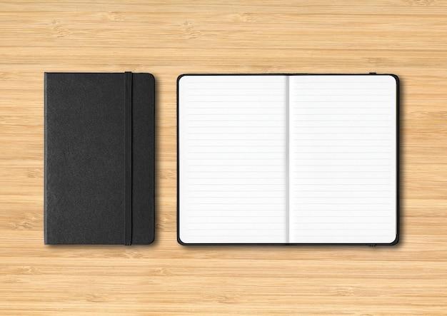 Zwart gesloten en open bekleed notitieboekjemodel dat op houten achtergrond wordt geïsoleerd