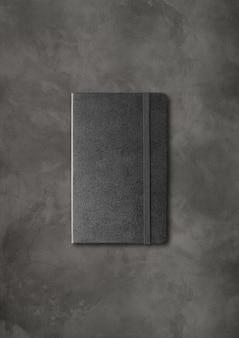 Zwart gesloten notitieboekjemodel dat op donker beton wordt geïsoleerd