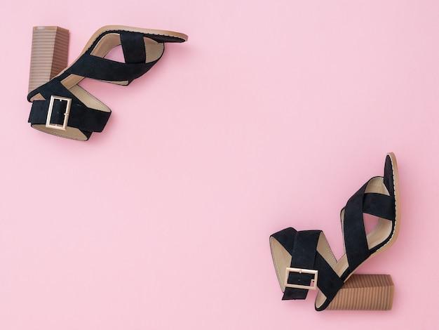 Zwart gevlochten damesschoenen op de hoeken van een roze achtergrond. mode damesschoenen.