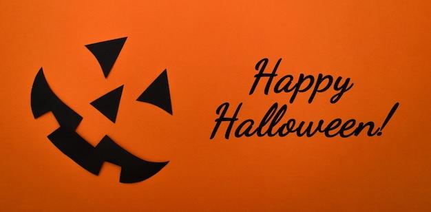 Zwart gezicht van zwart papier op een oranje achtergrond. halloween concept.