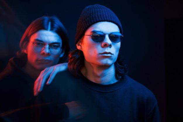 Zwart haar. portret van tweelingbroers. studio opname in donkere studio met neonlicht