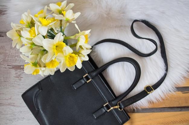 Zwart hahdbag en boeket van narcissen op witte vacht. in de mode