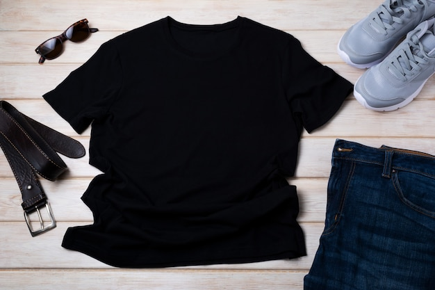 Zwart heren katoenen t-shirtmodel met grijze hardloopschoenen, donkere spijkerbroek, zonnebril en bruine leren riem. ontwerp t-shirt sjabloon, tee print presentatie mock up