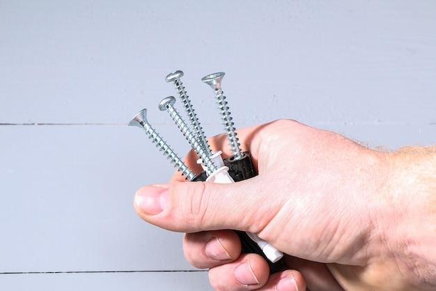 Zwart ijzeren schroeven, deuvelnagel in de palm voor hout. bevestigingsmiddelen en hardware in de hand.