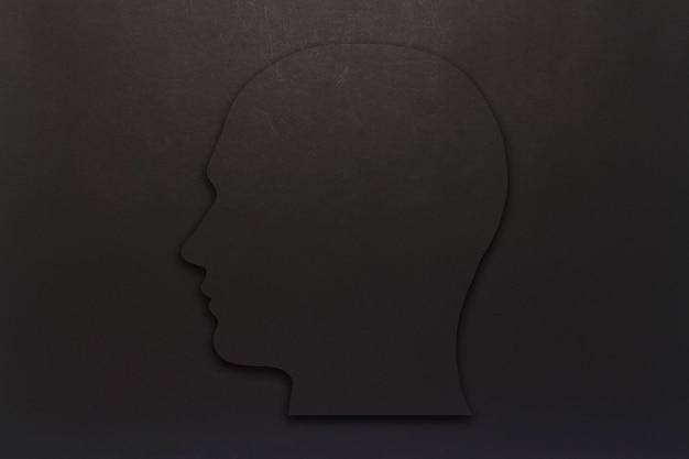 Zwart kartonnen hoofd op een zwarte achtergrond. kopieer ruimte. plat lag, bovenaanzicht.