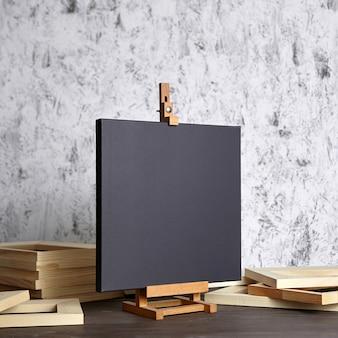 Zwart katoenen canvas op een houten ezel en brancard bars op tafel