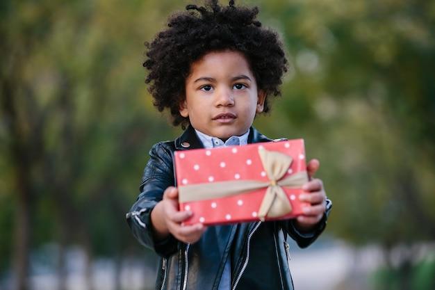 Zwart kind dat een rode gift met een onschuldige uitdrukking geeft. op de achtergrond van een park. kinderen en kerstmisconcept.