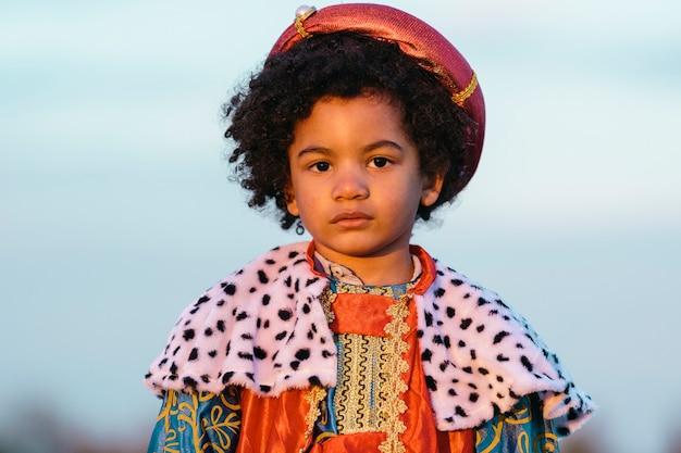 Zwart kind met afrohaar, gekleed in een wijze mannenkostuum, met een ernstige uitdrukking. kijkend naar de camera. op een hemelachtergrond. close-up shot. kinderen en kerstmisconcept.