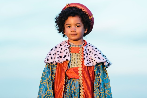 Zwart kind met afrohaar, gekleed in het kostuum van een wijze man. kijkend naar de camera. op een hemelachtergrond. gemiddeld schot. kinderen en kerstmisconcept.