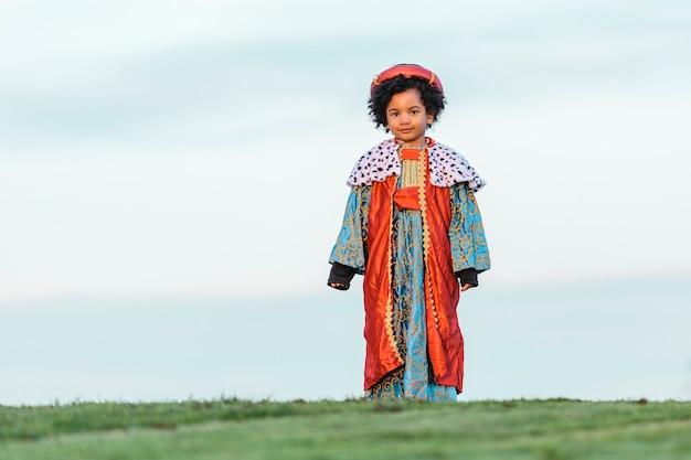 Zwart kind met afrohaar, gekleed in het kostuum van een wijze man. kijkend naar de camera. volledig schot. op een parkachtergrond. kinderen en kerstmisconcept.