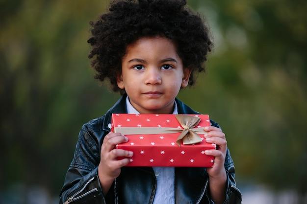 Zwart kind met een rode gift. op de achtergrond van een park. kinderen en kerstmisconcept.