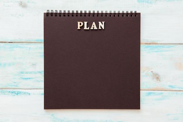 Zwart kladblok met het woordplan