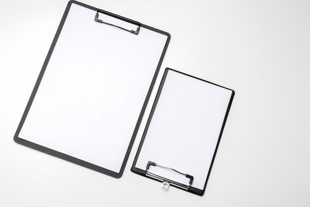 Zwart klembord met leeg wit blad bevestigd op wit