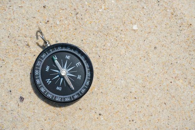 Zwart kompas op het strandzand