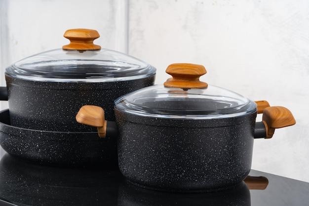 Zwart kookgerei op inductiefornuis tegen grijze muur