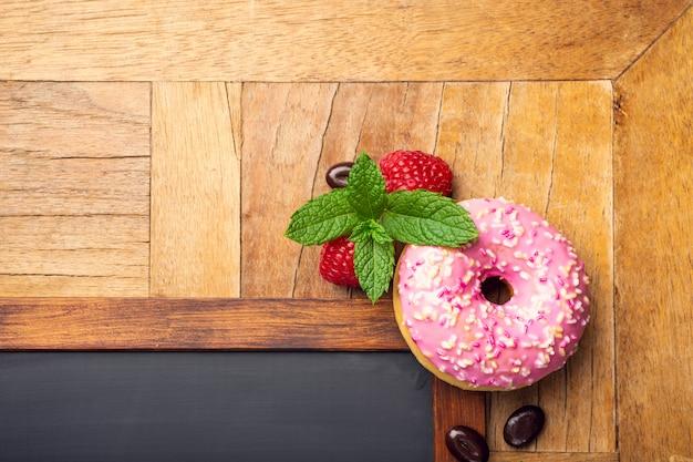 Zwart krijtbord met roze geglazuurde donut