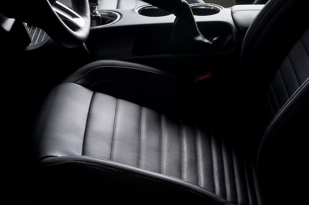Zwart lederen stoel voor bestuurder in een sportwagen, luxe details.