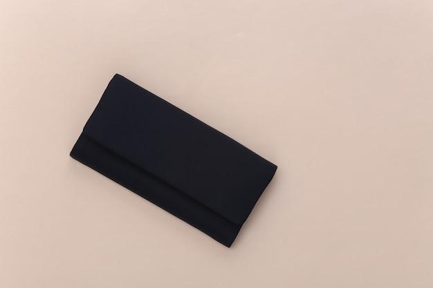 Zwart lederen vrouwelijke clutch handtas op beige achtergrond. bovenaanzicht