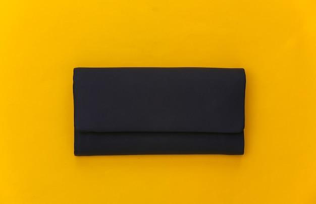 Zwart lederen vrouwelijke clutch handtas op gele achtergrond. bovenaanzicht