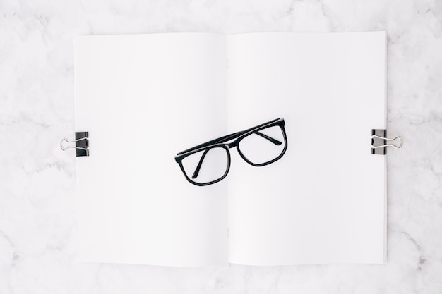 Zwart lenzenvloeistof over het witboek bevestigt met twee buldogklemmen op marmeren achtergrond