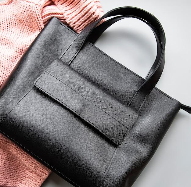 Zwart leren tas met gebreide trui op een grijze ondergrond