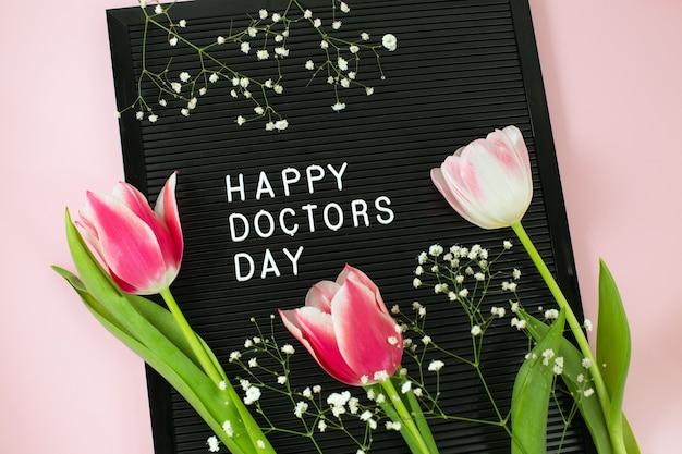 Zwart letterbord met witte plastic letters met opschrift happy doctor's day en bos roze tulpen op roze bureau.