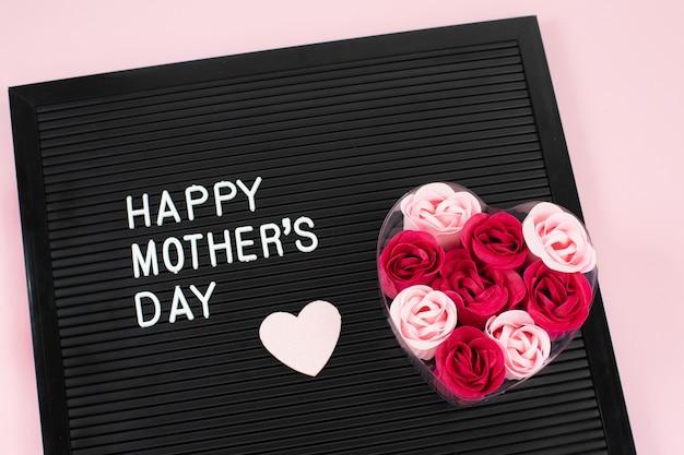 Zwart letterbord met witte plastic letters met opschrift happy mothers day en bloemenzeep, hart op roze bureau.