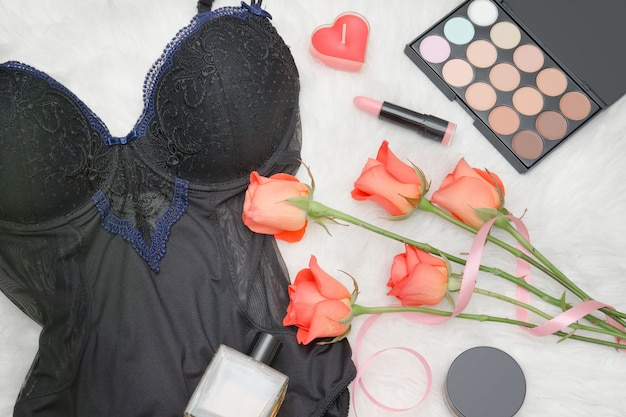 Zwart lichaam, oranje rozen, lippenstift, parfum en oogschaduw. modieus concept