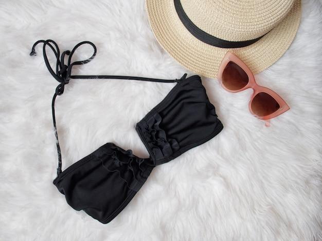 Zwart lijfje van een zwempak, bril en een hoed op witte vacht