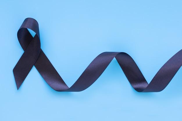 Zwart lintkrul op blauwe geïsoleerde achtergrond met exemplaarruimte, symbool van de voorlichtingsconcept van huidkanker.