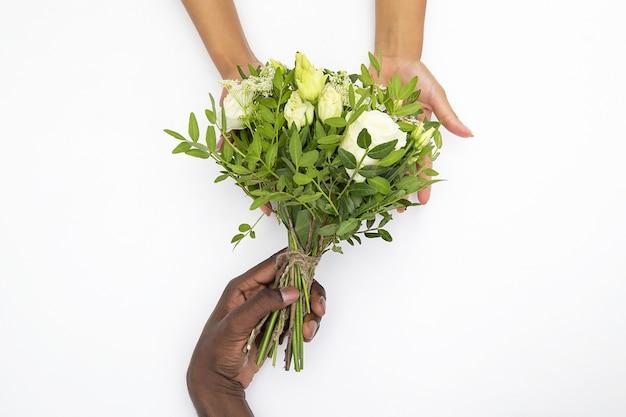 Zwart mannelijk en wit vrouwelijk de bloemboeket van de handholding