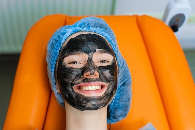 Zwart masker op meisjesgezicht voor koolstofpeeling. dermatologie en cosmetologie. met behulp van chirurgische laser.