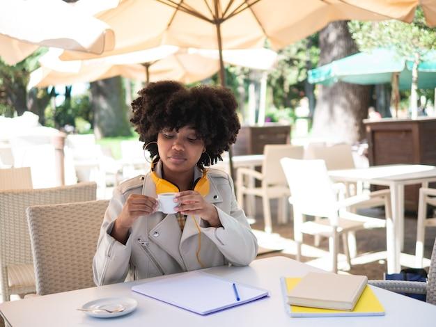 Zwart meisje dat een kopje koffie dronk terwijl ze aan het werk was, zat buiten aan een tafel op een bar