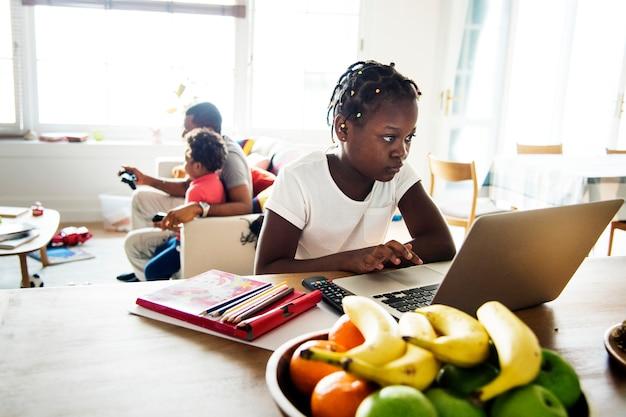 Zwart meisje die laptop thuis met behulp van