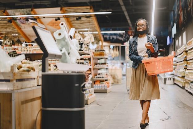 Zwart meisje in een masker koopt voedsel