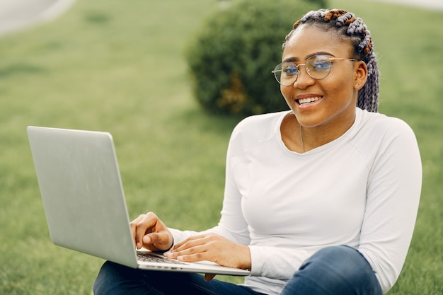 Zwart meisje in een zomerstad met laptop