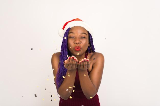 Zwart meisje in santa claus cap in feestelijke rode jurk blazen confetti