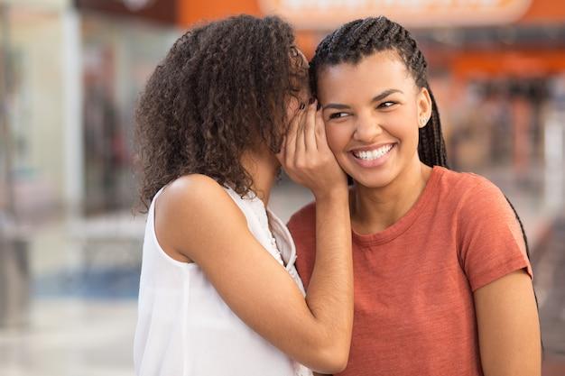 Zwart meisje whispering geheim naar lachend vriendin