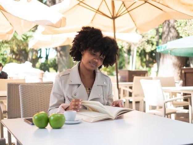 Zwart meisje zat op een terras een boek te lezen, verse appels op tafel