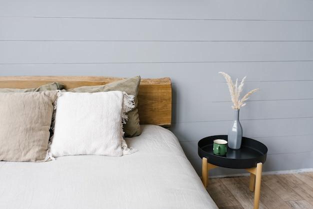 Zwart modern nachtkastje naast het tweepersoonsbed met grijs beddengoed in een eenvoudig slaapkamerinterieur