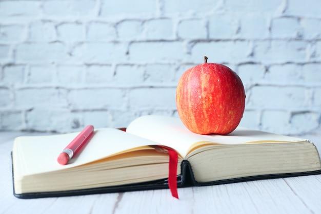 Zwart naar schoolconcept met appel op open boek op lijst.