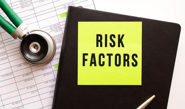 Zwart notitieboekje met gekleurde sticker met het opschrift risk factors. in de buurt is een phonendoscope. detailopname.