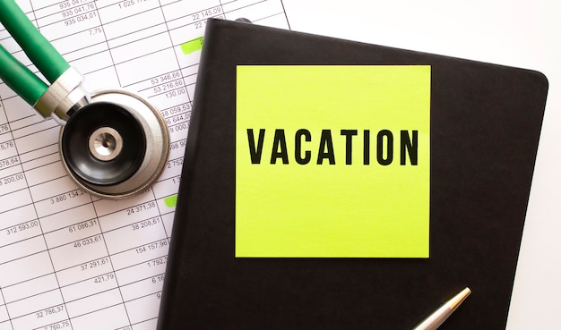 Zwart notitieboekje met gekleurde sticker met het opschrift vakantie. vlakbij is een phonendoscope. detailopname.