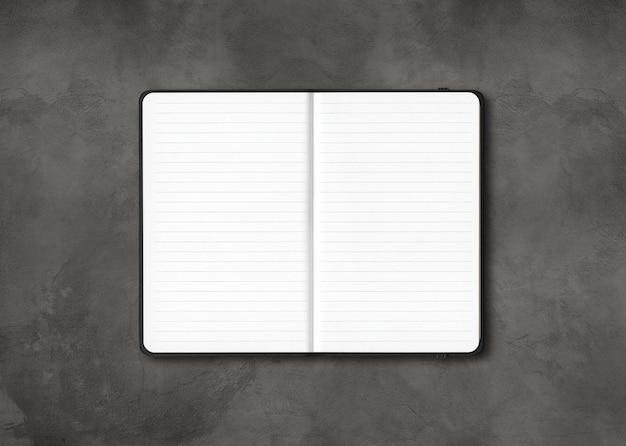 Zwart open bekleed notitieboekjemodel dat op donkere concrete achtergrond wordt geïsoleerd