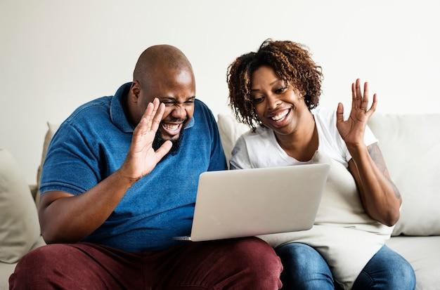 Zwart paar dat digitaal apparaat gebruikt