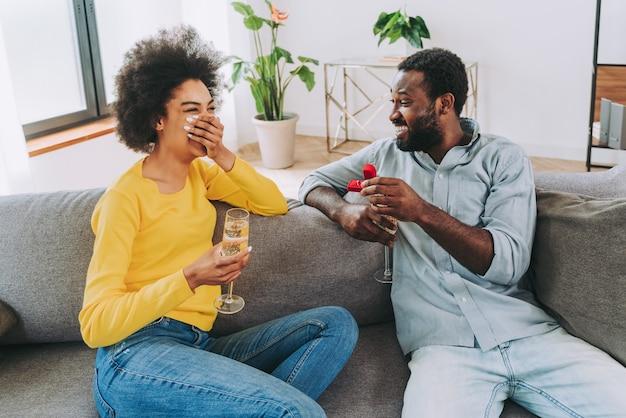 Zwart paar dat thuis mousserende wijn drinkt om te vieren - vrolijke paarbinding en aperitief