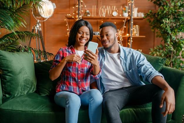 Zwart paar zittend op de bank en thuis op mobiele telefoon kijken. gelukkig afrikaanse liefde paar vrije tijd in hun huis, vrolijke familie samen ontspannen