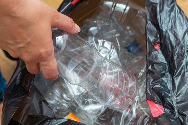 Zwart pakket met veel gebruikte plastic flessen voor recycling in handen